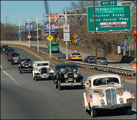 Motorcade proceeds with RFK banners in background.