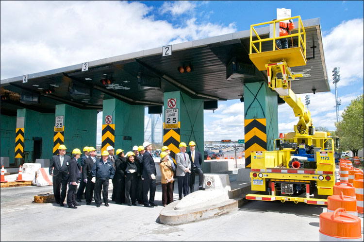 MTA Chairman Jay Walder (center in white hat) with elected officials watch as workers remove toll booth #1 sign from the first booths on the east-bound toll plaza that will be demolished in the coming weeks.