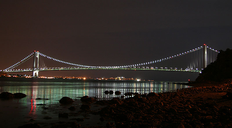 View from Staten Island shore of Verrazano-Narrows Bridge illuminated by energy-efficient and environmentally friendly LED necklace lights.