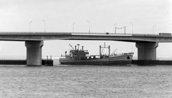 The Bowery Boy is seen passing under the 1970 Cross Bay Bridge. This photograph was used on the cover of the bridge's opening day brochure, May 28, 1970.