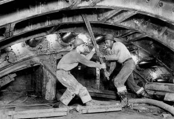 Sandhogs tightening a cast-iron tunnel lining bolt. Photographer: Michael Bobco for Somach Photo Service.