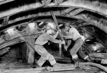 Sand hogs using a 5-foot ratchet wrench, tightening a cast-iron tunnel lining bolt. Photographer: Michael Bobco for Somach Photo Service. 2/26/1939