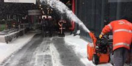 Employees clear snow from the LIRR station with snow thrower.