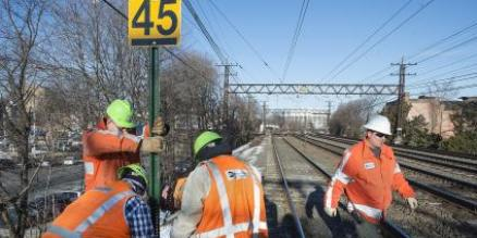 Metro-North track workers install speed restriction sign