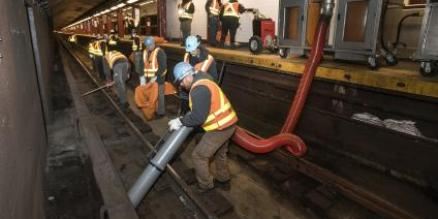Workers are testing one of two new prototypes of portable vacuum systems that the MTA is developing for use in station and track areas.