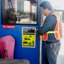 MTA Bridges and Tunnels Maintainer J.C. Hamilton installing poster at Throgs Neck Bridge